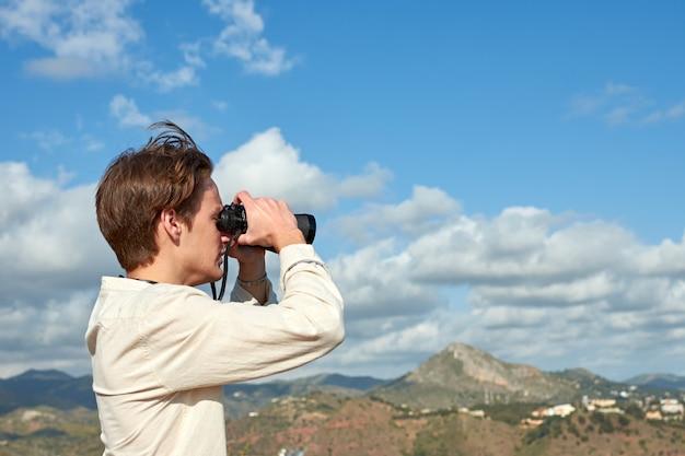 Une vue latérale d'un jeune voyageur d'espagne dans une chemise blanche à la recherche sur les montagnes à travers des jumelles