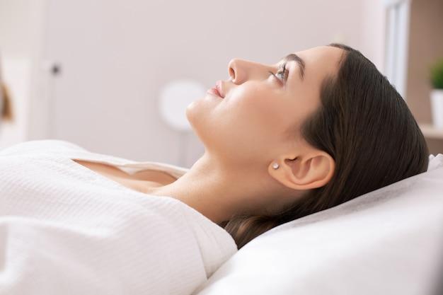 Vue latérale d'une jolie dame allongée et semblant calme en attendant le traitement