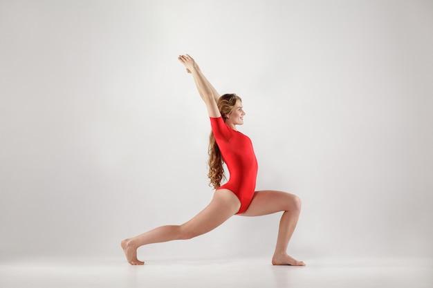 Vue latérale d'une jolie femme athlétique en justaucorps rouge faisant une pose de yoga fente en croissant