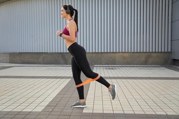 Vue latérale d'une jolie femme faisant des coups de pied arrière à l'aide d'élastiques de fitness en plein air. notion de sport. espace de copie