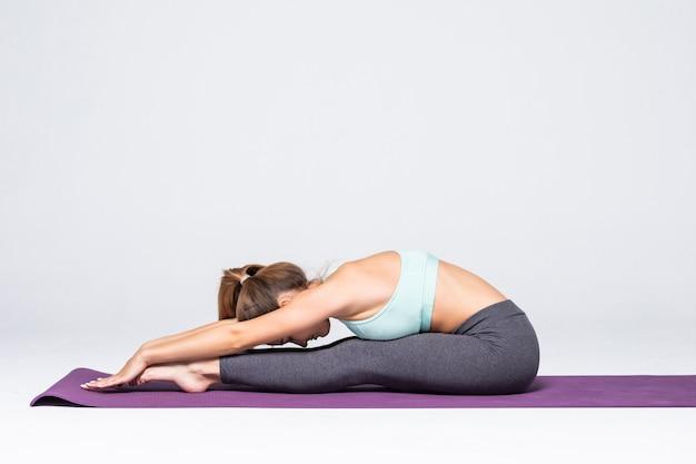 Vue latérale de la jolie jeune femme dans les vêtements de sport qui s'étend tout en faisant du yoga, isolé