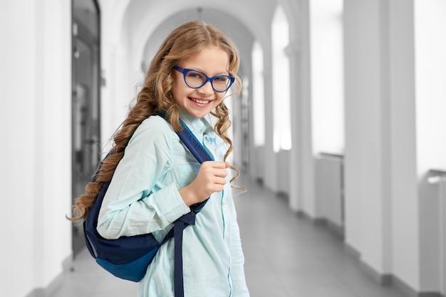 Vue latérale de la jolie petite fille avec sac à dos debout dans le couloir de l'école et rentrer à la maison après les cours.