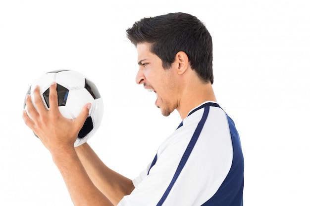 Vue latérale d'un joueur de football criant sur fond blanc