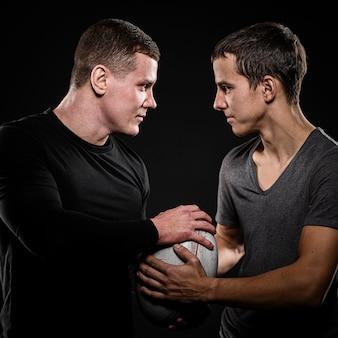 Vue latérale des joueurs de rugby masculins tenant le ballon avec les mains