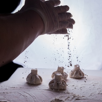 Vue latérale khinkali avec de la farine et la main de l'homme