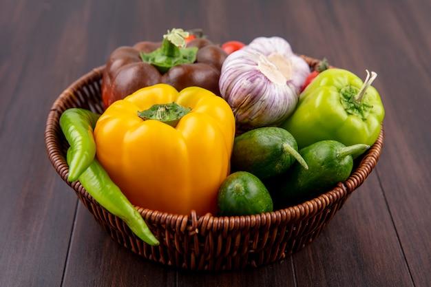 Vue latérale des légumes comme l'ail concombre tomate poivron dans le panier sur bois