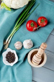 Vue latérale des légumes comme l'ail de tomate échalote avec du poivre noir sur le tissu et le broyeur d'ail sur fond de bois