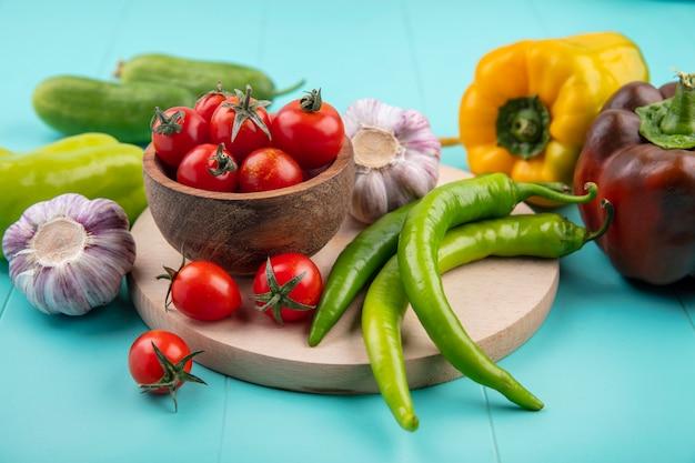 Vue latérale des légumes comme bol de tomate ail poivron sur une planche à découper avec des concombres sur bleu