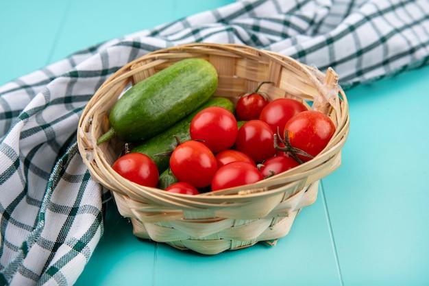 Vue latérale des légumes comme concombre tomate dans le panier sur tissu à carreaux sur bleu