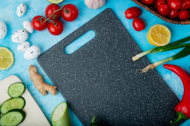 Vue latérale des légumes comme la tomate au gingembre et d'autres avec du citron et une planche à découper sur la surface bleue
