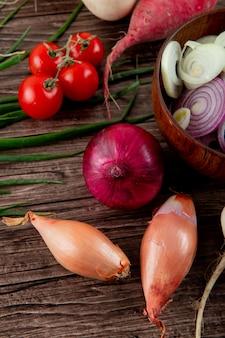 Vue latérale des légumes comme la tomate oignon échalote et d'autres sur fond de bois