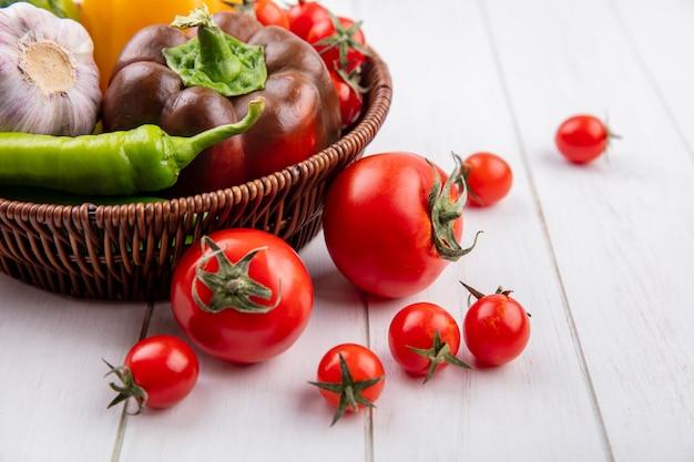Vue latérale des légumes comme tomate poivrée ail dans le panier et sur bois