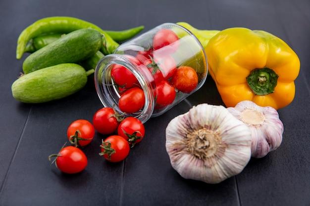 Vue latérale des légumes comme des tomates débordant de concombre ail et poivron sur fond noir