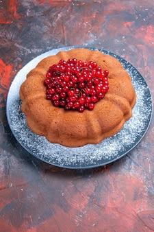 Vue latérale de loin un délicieux gâteau au dessert et des groseilles rouges sur la table rouge-bleu