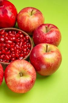 Vue latérale de loin les fruits le bol de pommes appétissant de graines de grenade sur la table