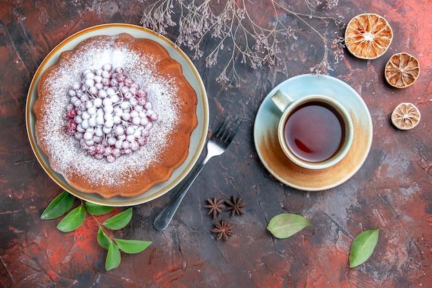 Vue latérale de loin un gâteau un gâteau avec des feuilles de baies une fourchette de citron une tasse de thé à l'anis étoilé
