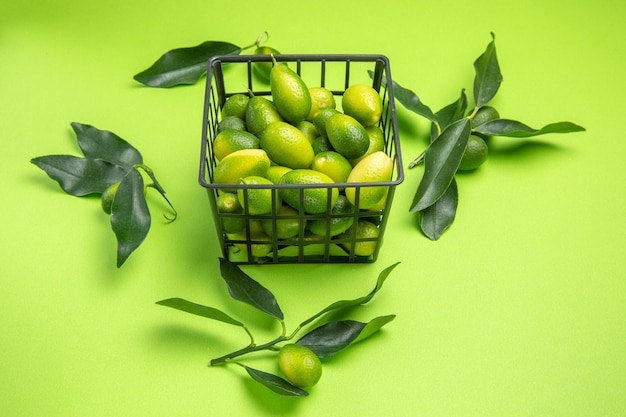 Vue latérale de loin panier d'agrumes avec des feuilles vertes d'agrumes sur la table verte