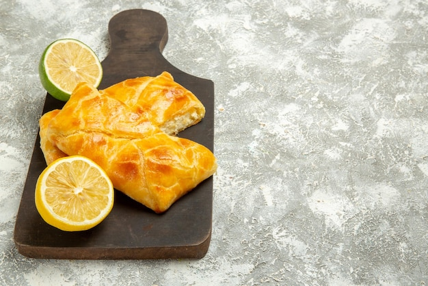Vue latérale de loin tartes et tartes appétissantes au citron sur la planche à découper sombre à côté du citron vert sur le côté gauche de la table