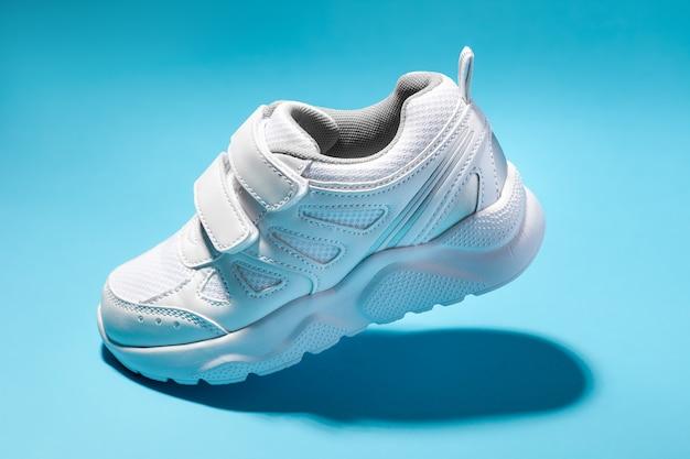 Vue latérale macro un enfant blanc volant des chaussures de course avec des attaches velcro isolées sur un fond bleu