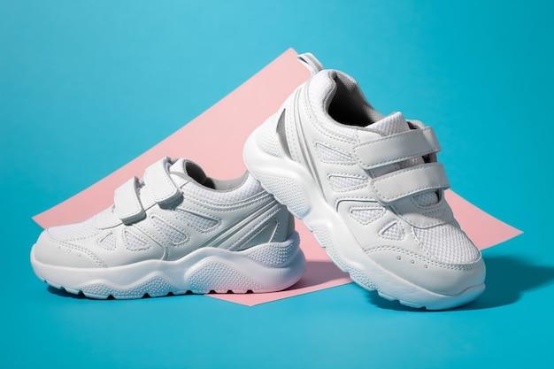 Vue latérale macro, une sneaker blanche pour enfant se dresse à l'arrière de la deuxième sneaker sur un carré géométrique...