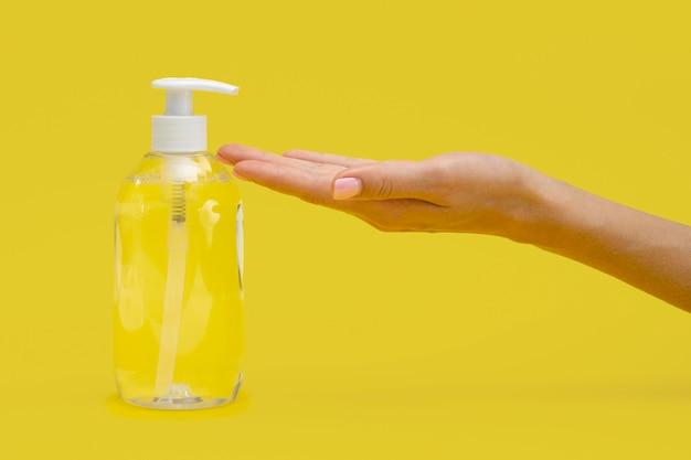 Vue latérale de la main à l'aide de savon liquide