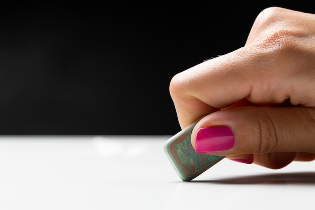Vue latérale de la main avec gomme à effacer