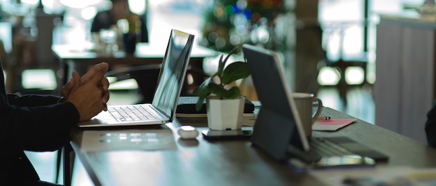 Vue latérale de la main d'homme d'affaires travaillant avec un ordinateur portable sur une table de réunion avec des fournitures de bureau