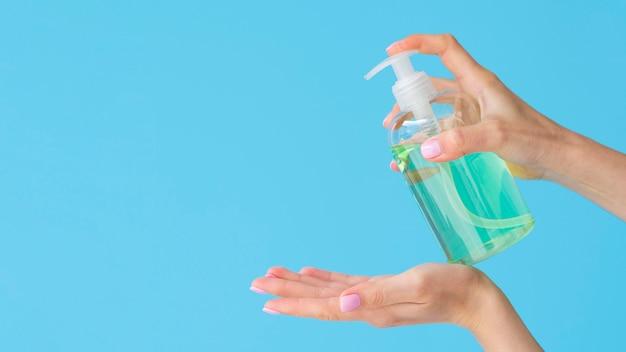 Vue latérale des mains à l'aide de savon liquide avec espace copie