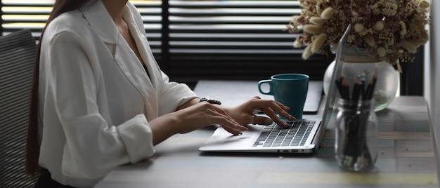 Vue latérale des mains féminines tapant sur ordinateur portable alors qu'il était assis à l'espace de travail à côté de la fenêtre dans la salle de bureau