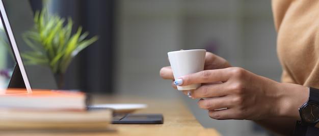 Vue latérale des mains féminines tenant une tasse de café tout en travaillant sur une barre en bois avec tablette et livre