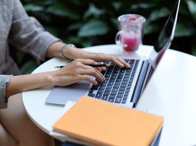 Vue latérale des mains féminines travaillant avec ordinateur portable sur table basse avec ordinateur portable et paperasse au café