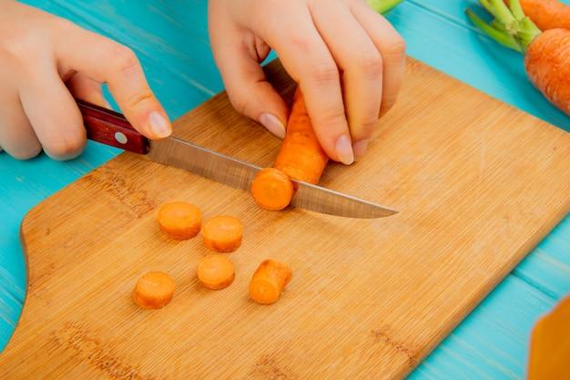 Vue latérale des mains de femme coupe la carotte sur une planche à découper avec un couteau sur fond bleu
