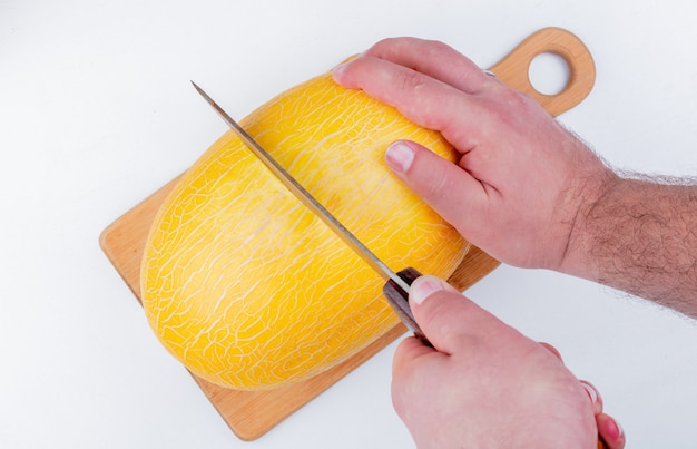 Vue latérale des mains mâles coupant le melon avec un couteau sur une planche à découper sur fond blanc
