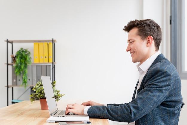 Vue latérale mâle adulte travaillant sur ordinateur portable