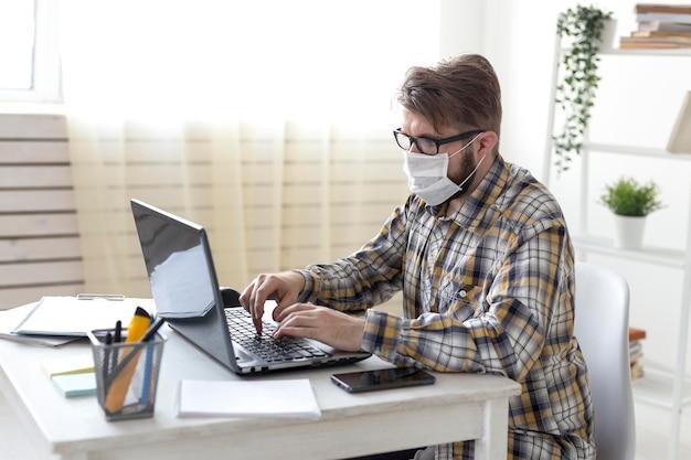 Vue latérale mâle travaillant à domicile sur ordinateur portable