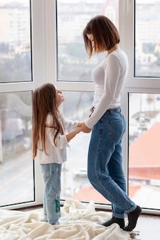 Vue latérale maman et fille se tenant la main