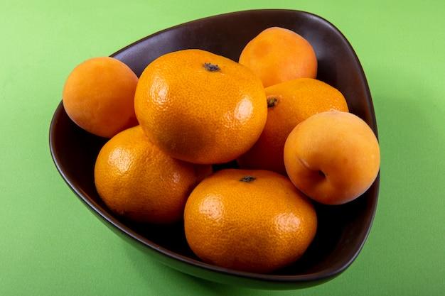 Vue latérale des mandarines dans un bol sur vert clair