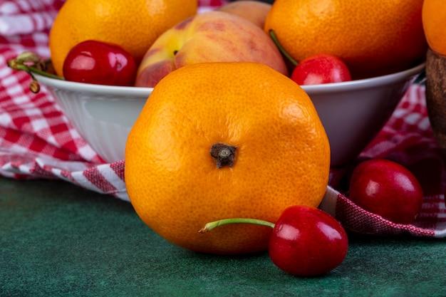 Vue latérale de mandarines mûres fraîches avec des cerises rouges sur dark