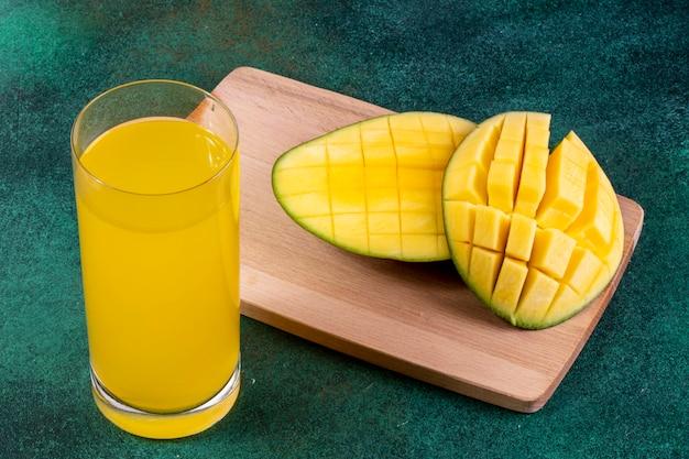 Vue latérale de la mangue en tranches sur un tableau noir avec un verre de jus d'orange sur une table verte