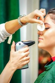 Vue latérale d'un maquilleur utilisant un aérographe faisant un fond de teint à l'aérographe sur un visage féminin