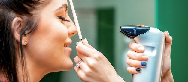 Vue latérale d'une maquilleuse utilisant un aérographe faisant un fond de teint à l'aérographe sur un visage féminin i...