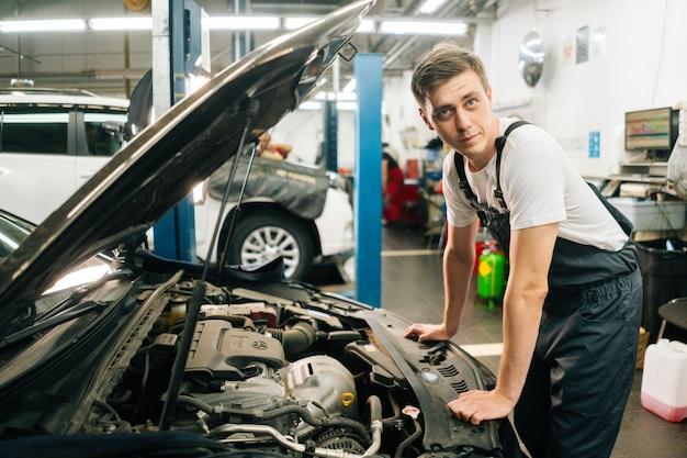 Vue latérale d'un mécanicien automobile professionnel beau et confiant en uniforme bleu, debout devant ...