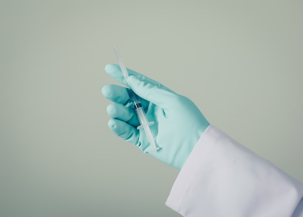 Vue latérale médecin avec des gants tenant la seringue à la main. horizontal