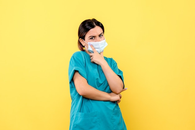 Vue latérale d'un médecin en masque un médecin en masque envisage de traiter des patients atteints de covid