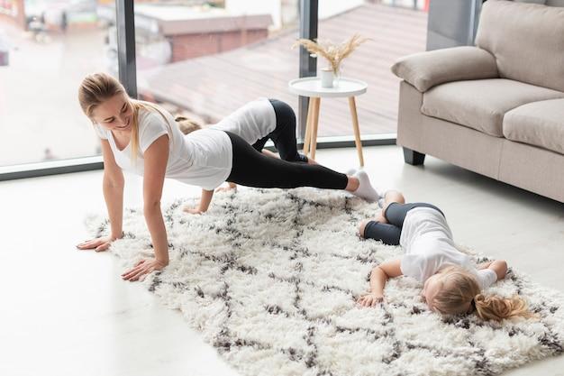 Vue latérale de la mère exerçant à la maison avec les filles