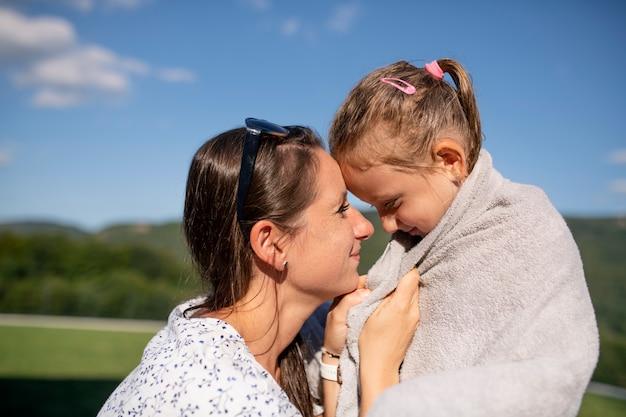 Vue latérale d'une mère séchant sa fille avec un towwl à l'extérieur après la baignade.