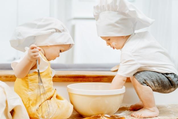 Vue latérale d'un mignon petit cuisinier, des enfants en chapeaux avec intérêt préparent la pâte assis sur une table dans la cuisine. concept d'enfants aides travailleurs et travailleurs. devoirs pour les enfants