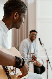 Vue latérale des musiciens masculins à la maison à jouer de la guitare