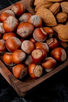 Vue latérale de noisettes aux amandes en coque sur fond de bois