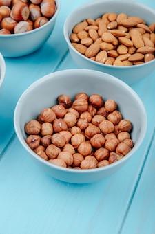 Vue latérale des noisettes aux amandes dans des bols sur fond bleu